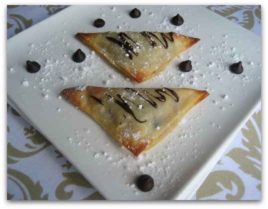 Chocolate Chip Cookie Dough Dessert Wontons on a plate with powdered sugar and chocolate chips