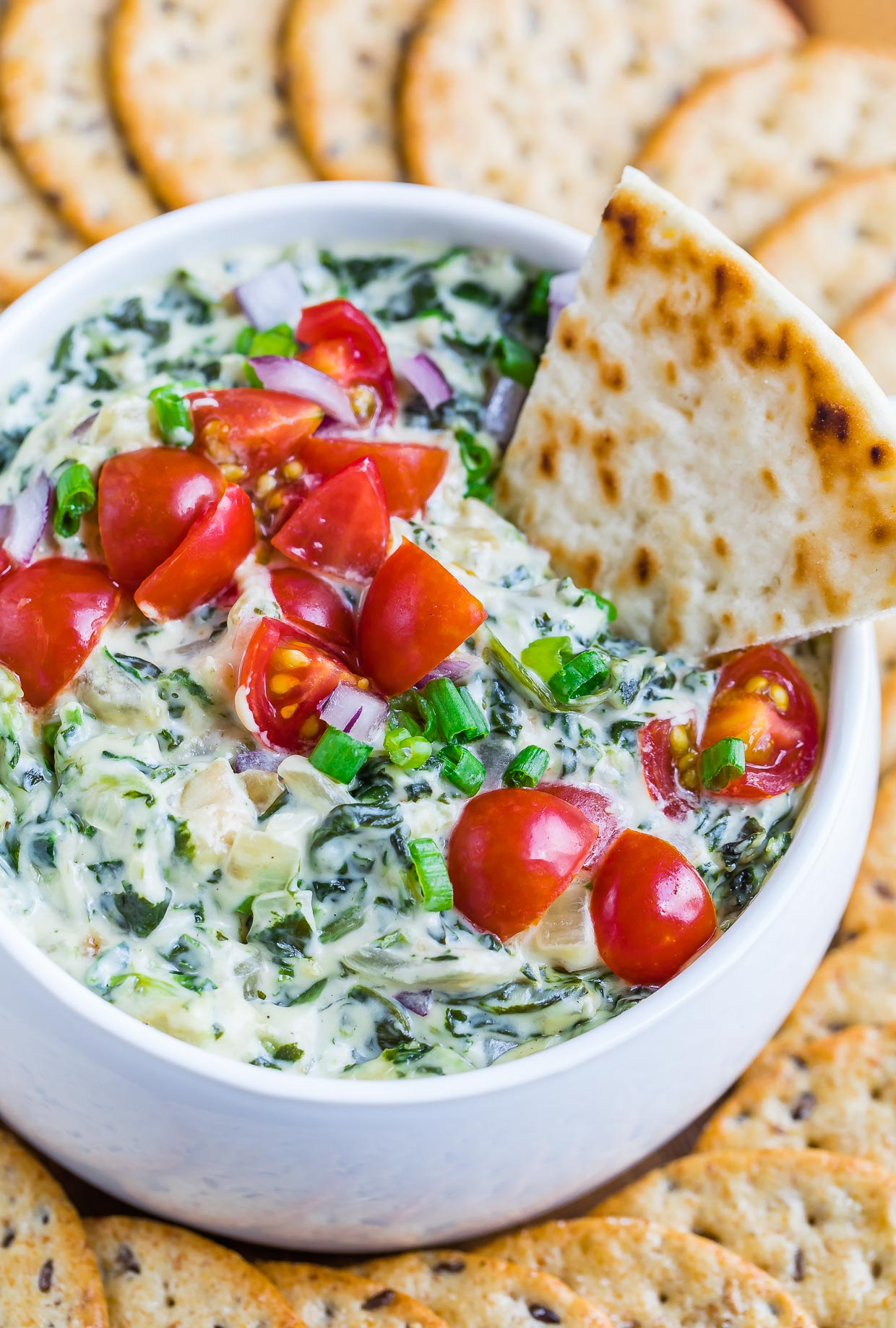 This healthy hot spinach artichoke dip is going to rock your world! Dive in with a few pita chips and a pile of crunchy veggies and be prepared to hover over the bowl until it's gone!