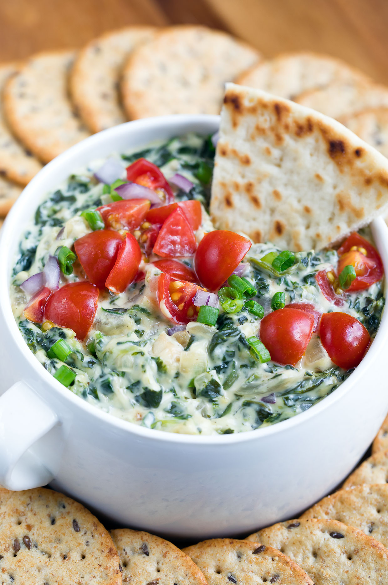 This healthy hot spinach artichoke dip is going to rock your world! Dive in with a few toasty chips and a pile of crunchy veggies and be prepared to hover over the bowl until it's gone!