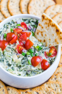 This healthified spinach artichoke dip is going to rock your world! Dive in with a few toasty chips and a pile of crunchy veggies and be prepared to hover over the bowl until it's gone!