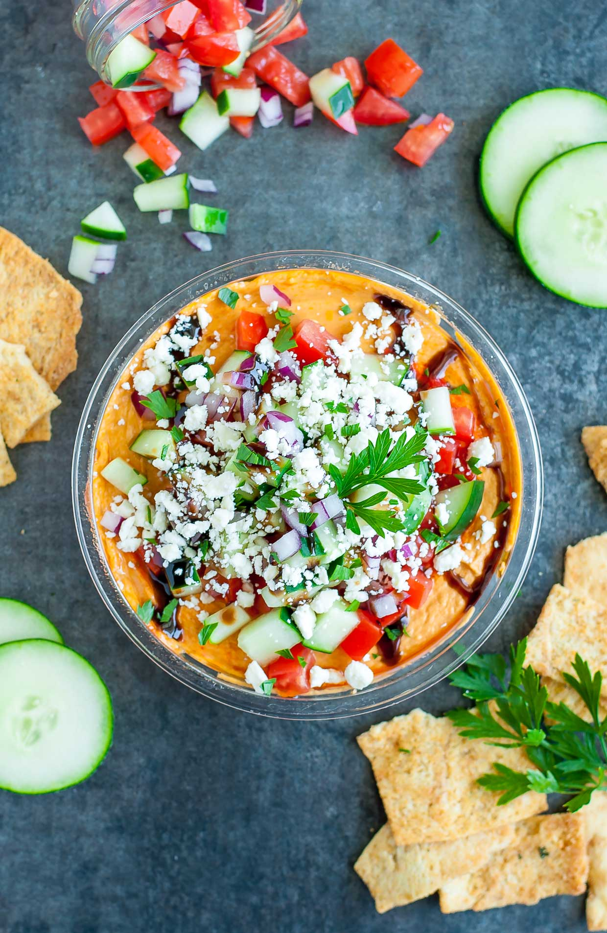 party hummus. Tasty hummus is piled high with a mountain of toppings including feta, cucumber, onion, parsley, and drizzled with a sweet and savory balsamic glaze.