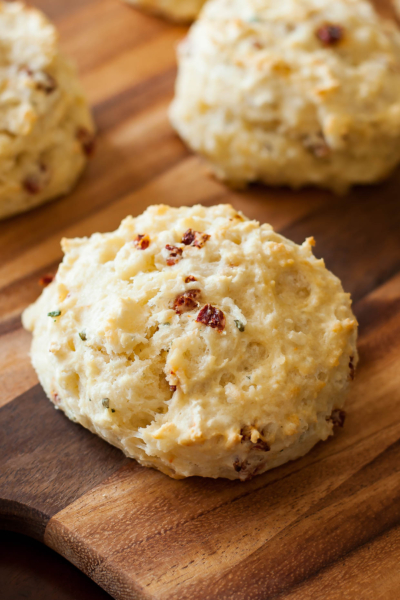Asiago Sun-dried Tomato Biscuits are fluffy, flaky biscuits flecked with sun-dried tomato and asiago cheese, then slathered in a homemade whipped basil butter.