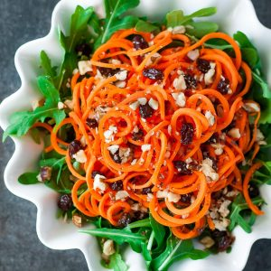 This healthy carrot salad is spiralized into crunchy carrot noodles and served atop a bed of mixed greens with juicy raisins, crisp candied walnuts, and a homemade lemon honey dijon dressing! No spiralizer? No problem! It worksgreat with shredded carrots too!