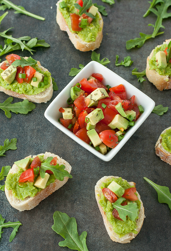 Sweet Pea Crostini with Tomato and Avocado :: This tasty appetizer is a great way to add some extra vegetables to the mix! Making use of delicious seasonal produce, these tomato avocado sweet pea crostini are quick, easy, and ridiculously good!