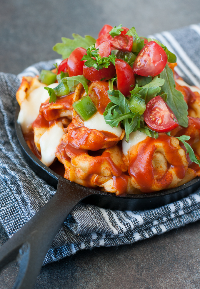Easy, cheesy tortellini with a twist! :: This feisty Mexican Baked Tortellini is quick, easy, and utterly delicious piled high with all your favorite toppings!