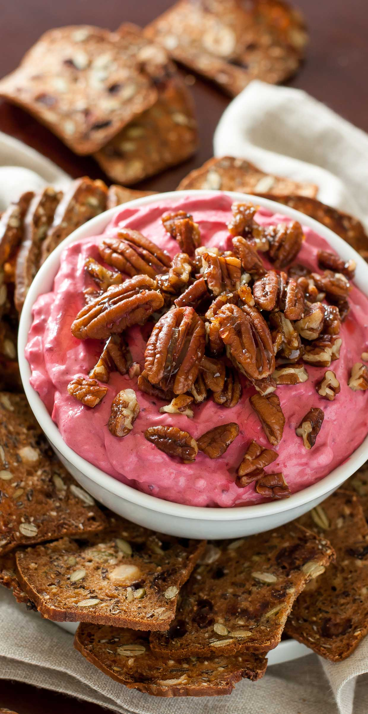 This fun and festive cranberry dip is swirled with cream cheese and honey and topped with the most delicious candied pecans. It's perfect for all your holiday needs from parties to potlucks to family gatherings galore!