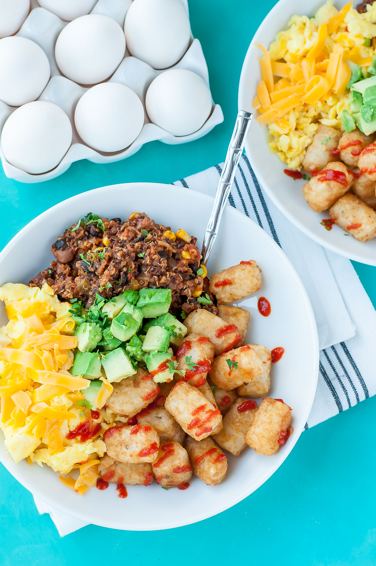 Cheesy scrambled eggs paired with a flavorful vegetarian quinoa chili, fresh avocado, and spicy sriracha tots... These vegetarian chili tot breakfast bowls are ready to rock your face!