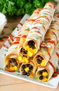 Cheesy Black Bean Flautas :: cheesy black beans and corn rolled up in a flour tortilla and baked to crispy perfection!