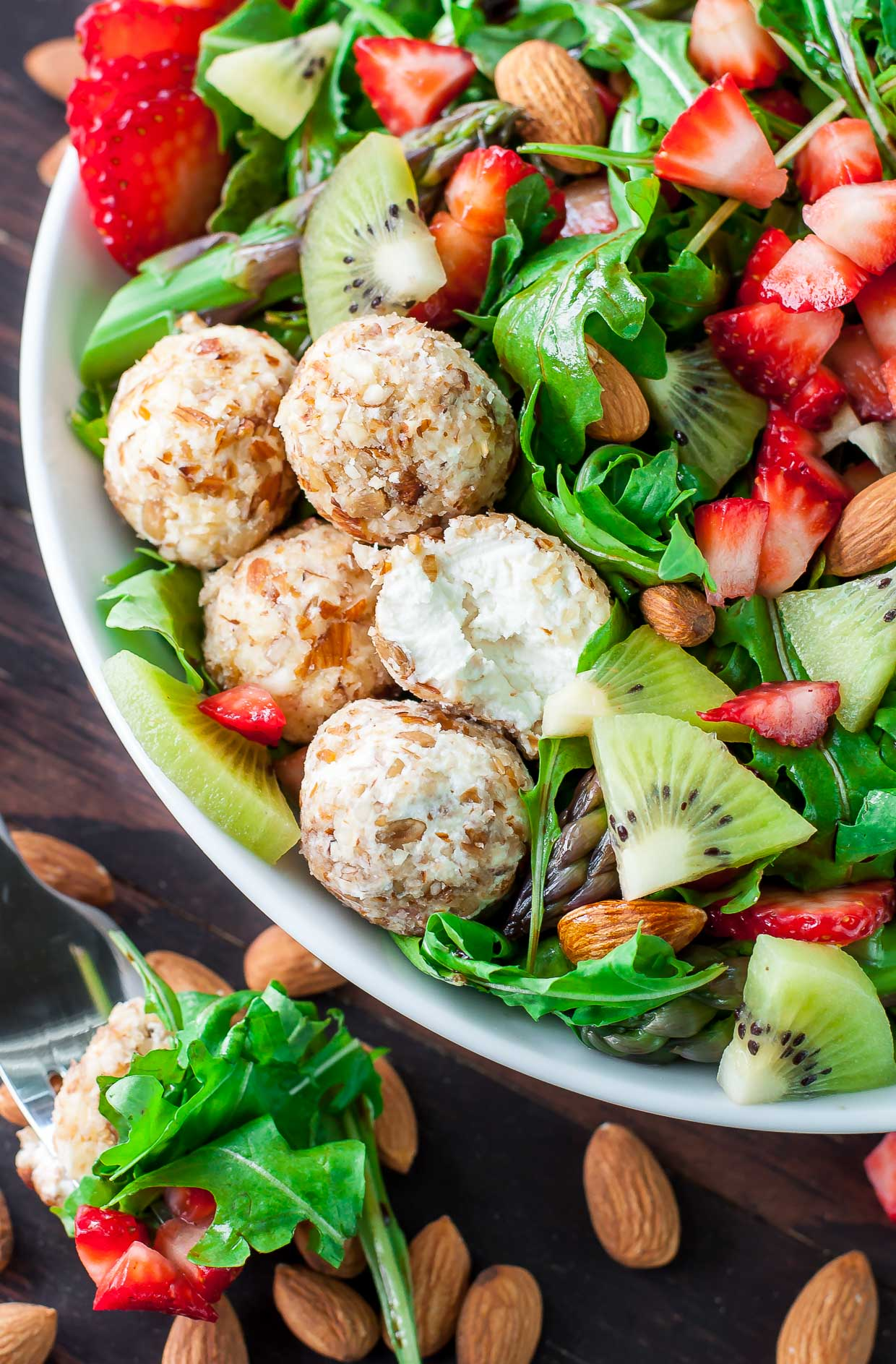 Just say no to boring salads! This sweet and savory Almond Crusted Goat Cheese Salad is flecked with strawberries and kiwi and topped with a fruity balsamic dressing.