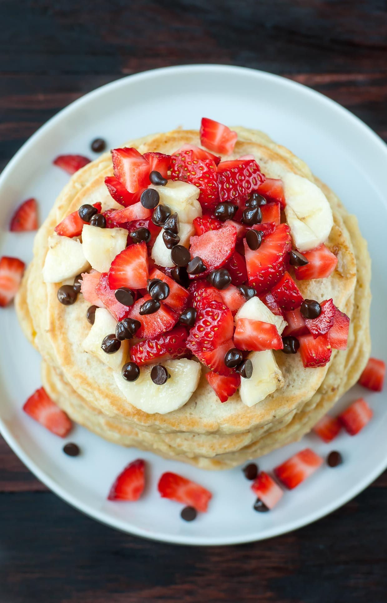 Perfectly fluffy pancakes topped with banana, strawberries, and a kiss of dark chocolate chips, these Banana Split Pancakes are a healthy spin on dessert pancakes!