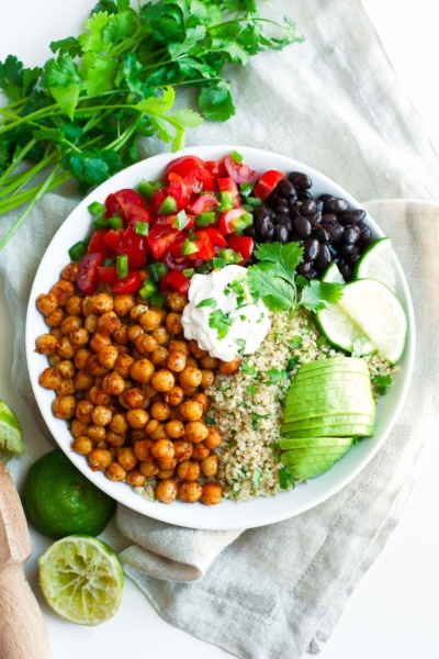 roasted chickpea quinoa taco salad in white bowl with lime wedges