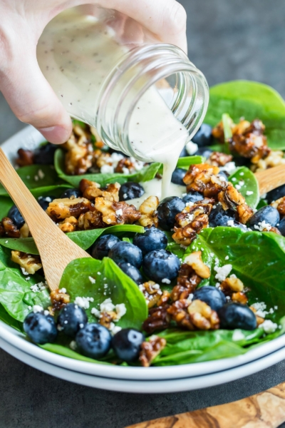 Lemon poppyseed dressing poured over blueberry spinach salad