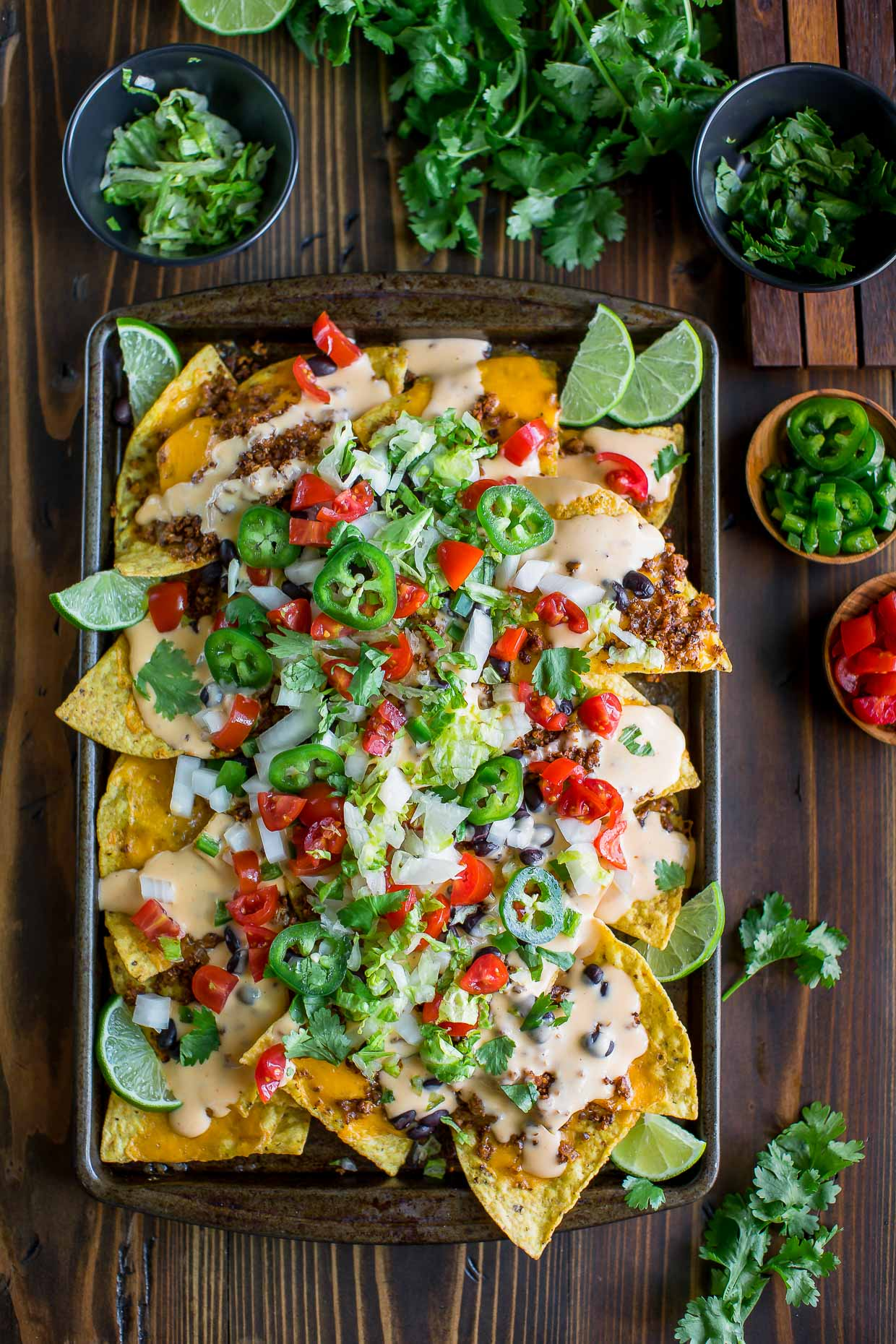 easy cheesy nachos on a sheet pan with homemade queso