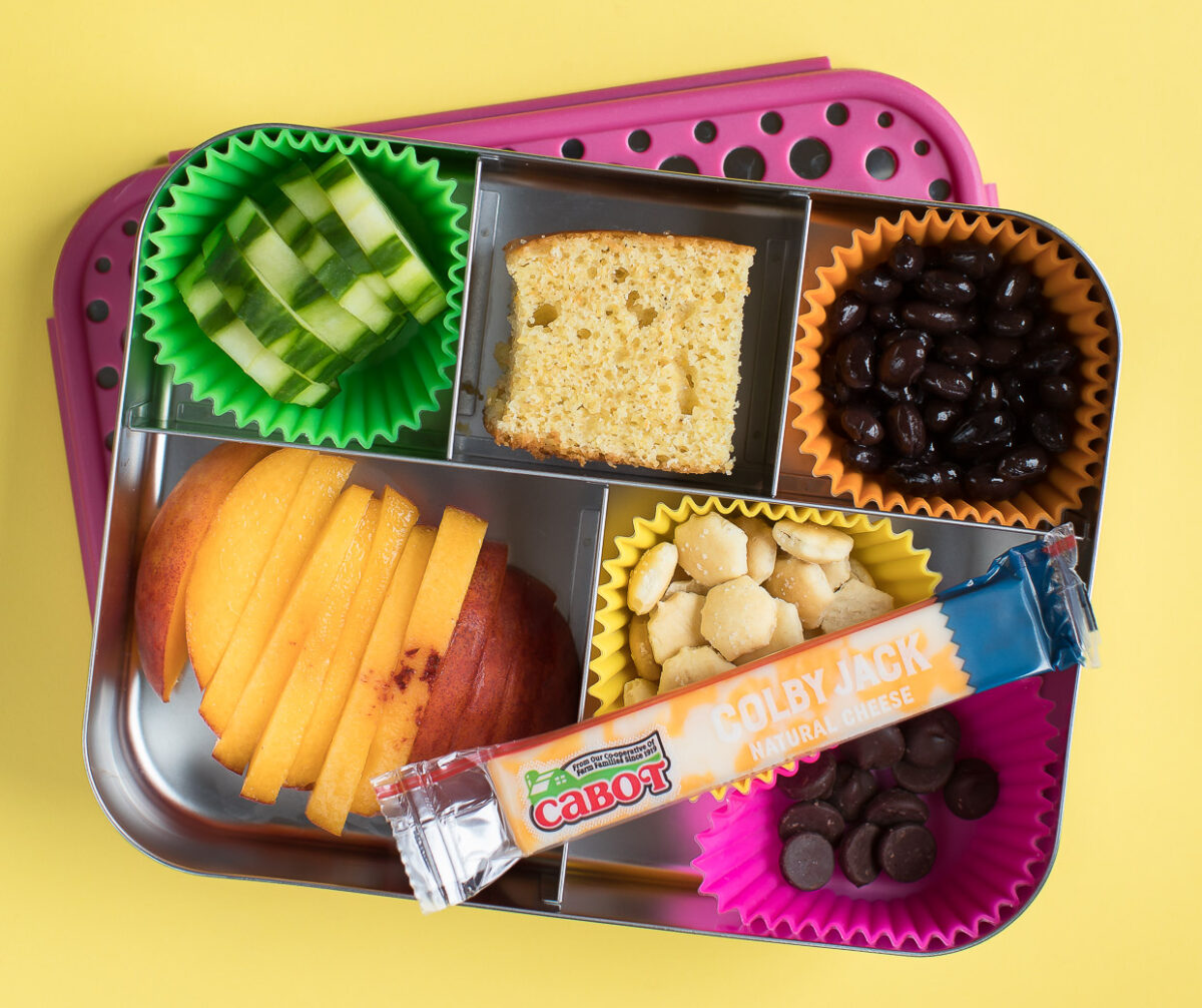 Bento Box Lunch with Cornbread, Cheese, Black Beans, Cucumber, Peach, Crackers